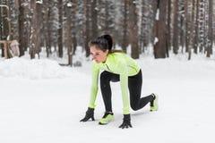 Geeignete Frau in der Position bereit, Winterpark draußen laufen zu lassen stockfoto