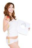Geeignete Frau der Seitenansicht mit einem Apfel und einem Gewicht Stockfotos