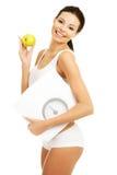 Geeignete Frau der Seitenansicht mit einem Apfel und einem Gewicht Lizenzfreies Stockfoto