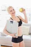 Geeignete Frau in der Sportkleidungsholdingskala und Apfel im Eignungsstudio Lizenzfreie Stockfotografie