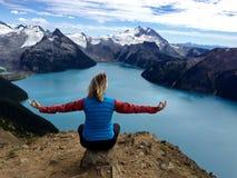 Geeignete Frau in der Yoga-Haltung am alpinen See umgeben mit Schnee mit einer Kappe bedeckten Bergen Lizenzfreie Stockfotografie