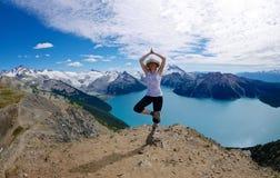 Geeignete Frau in der Yoga-Haltung am alpinen See umgeben mit Schnee mit einer Kappe bedeckten Bergen Lizenzfreie Stockfotos