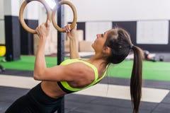 Geeignete Frau des Athleten, die in der Turnhalle hochzieht auf Seitenansicht der gymnastischen Ringe trainiert Stockbild