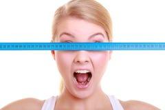 Geeignete Frau des Eignungsmädchens, die ihre Augen mit messendem Band bedeckt Lizenzfreies Stockbild