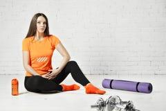 Geeignete Frau des Sports, die in einer Turnhalle mit Ausrüstung, Dummkopf und Ausbildungsauflage aufwirft Stockfotos