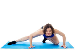 Geeignete Frau, die auf blauer Matte, Atelieraufnahme sich duckt Lizenzfreies Stockfoto
