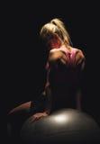 Geeignete Frau, die auf einem Yoga-Ball sitzt Lizenzfreies Stockbild