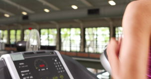 Fit woman running on treadmill with trainer timing her Stock Footage