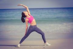 Geeignete Frau, die das Ausdehnen auf dem Strand macht Stockfoto