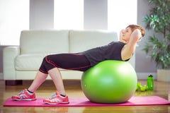 Geeignete Frau, die das Handeln sitzt, ups auf Übungsball Stockfoto