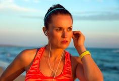Geeignete Frau, die den Abstand untersucht und Musik hört Stockbilder