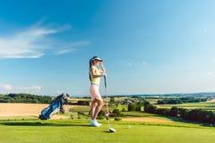 Geeignete Frau, die den Horizont auf dem grünen Gras eines Golfplatzes betrachtet Stockfotos