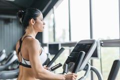 Geeignete Frau, die elliptischen Trainer in der modernen Turnhalle verwendet lizenzfreies stockfoto