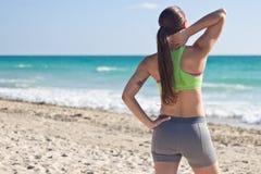 Geeignete Frau, die nach einem Lauf auf dem Strand stillsteht Lizenzfreies Stockfoto