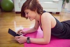 Geeignete Frau, die Tabletten-PC auf Matte verwendet Lizenzfreies Stockbild