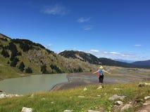 Geeignete Frau, die Veiw von alpinem See umgeben mit Bergen genießt Stockbild