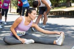 Geeignete Frau, die vor Rennen aufwärmt Stockfotografie