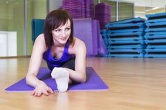 Geeignete Frau, die Yogaübung auf einer Matte in einer Turnhalle tut Stockbild