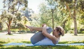 Geeignete Frau, die Yoga im Park tut Stockfotos