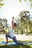 Geeignete Frau, die Yoga im Park tut Lizenzfreies Stockbild