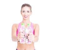 Geeignete Frau, die zwei Flaschen Wasser zeigt Lizenzfreie Stockbilder