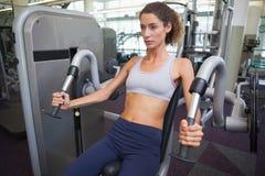 Geeignete Frau, welche die Gewichtsmaschine für ihre Arme verwendet Stockbild