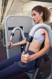 Geeignete Frau, welche die Gewichtsmaschine für ihre Arme verwendet Stockfoto