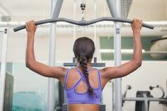 Geeignete Frau, welche die Gewichtsmaschine für ihre Arme verwendet Lizenzfreie Stockbilder