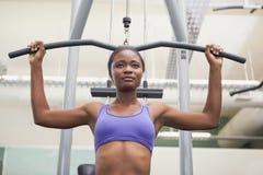 Geeignete Frau, welche die Gewichtsmaschine für ihre Arme verwendet Lizenzfreies Stockbild