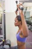 Geeignete Frau, welche die Gewichtsmaschine für ihre Arme verwendet Lizenzfreie Stockfotos