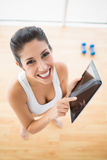 Geeignete Frau, welche die Tablette macht eine Pause vom Training lächelt an Ca verwendet Lizenzfreie Stockfotografie