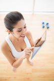 Geeignete Frau, welche die Tablette macht eine Pause vom Training verwendet Stockbilder