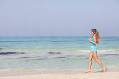 Geeignete gesunde Frau, die auf Küste rüttelt oder läuft Stockfotografie