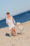 Geeignete gesunde Frau, die mit Hund läuft Stockfoto