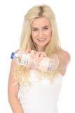 Geeignete gesunde glückliche junge Blondine, die eine Flasche Mineralwasser halten lizenzfreie stockbilder