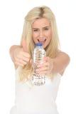 Geeignete gesunde glückliche junge Blondine, die eine Flasche Mineralwasser halten stockfotos