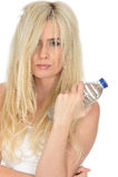 Geeignete gesunde junge natürliche Blondine, die eine Flasche Mineralwasser halten stockfoto