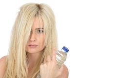 Geeignete gesunde junge natürliche Blondine, die eine Flasche Mineralwasser halten lizenzfreies stockbild