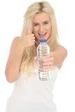 Geeignete gesunde positive glückliche junge Blondine, die eine Flasche Mineralwasser halten stockfoto