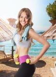 Geeignete glückliche Frau, die auf dem Strand ausarbeitet Lizenzfreies Stockfoto