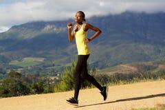 Geeignete junge afrikanische Frau, die draußen in der Natur rüttelt Stockbild