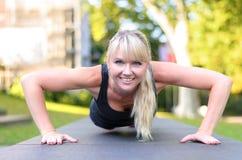 Geeignete junge blonde Frau, die Übungen in einem Park tut Stockbilder