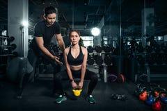 Geeignete junge Frau in der Sportkleidung konzentrierte sich auf das Anheben eines Dummkopf duri lizenzfreies stockfoto