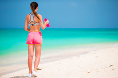 Geeignete junge Frau des Active in ihrer Sportkleidung während der Strandferien Stockfotos