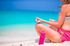 Geeignete junge Frau des Active in Yogaposition an ihrer Sportkleidung während der Strandferien Stockbild