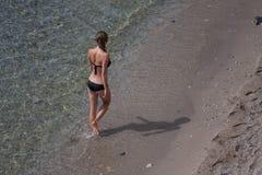 Geeignete junge Frau, die den schwarzen Bikini geht durch Strand trägt stockbild