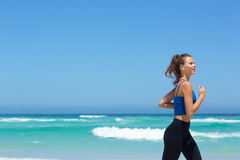 Geeignete junge Frau, die durch das Meer läuft Lizenzfreie Stockfotos