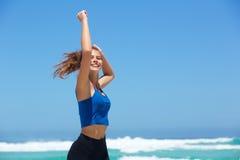 Geeignete junge Frau, die durch das Meer mit den Armen angehoben läuft Stockbild