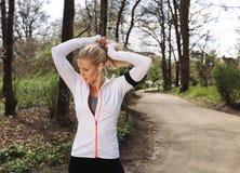 Geeignete junge Frau, die für ihren Lauf im Wald sich vorbereitet Stockfotos