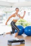 Geeignete junge Frau, die Stepp-Aerobic-Übung durchführt Stockbilder